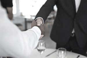 Businesspeople making handshakes, at restaurant