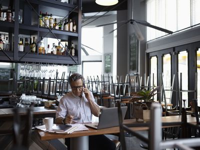 Businessman working on paperwork in a empty bar with upturned chairs
