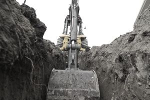 heavy equipment using a bucket to completed a trench excavation.