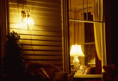 an exterior house photo of a living room with a lamp on