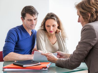 Couple reviewing a lease agreement with a female landlord