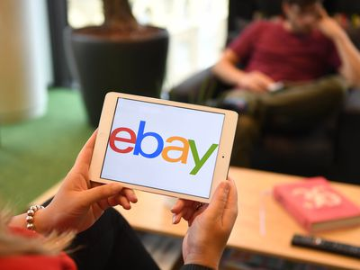 a woman holding a tablet with an ebay logo