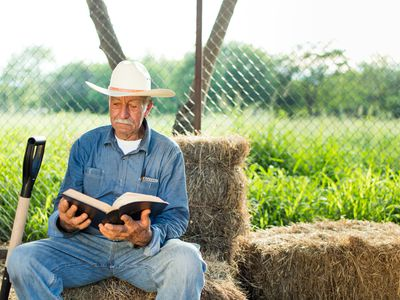 Farmer in all denim and a cowboy hat sitting on a hay bale reading a book