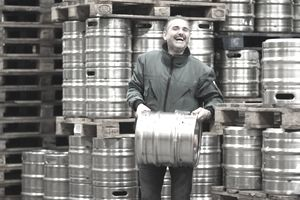 Smiling man carrying a reusable beer keg in a warehouse full of kegs on pallets.