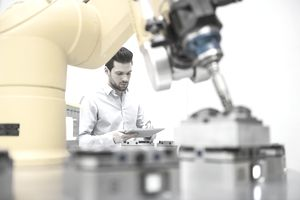 Young businessman checking automated production in factory