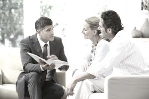 salesman showing couple a brochure