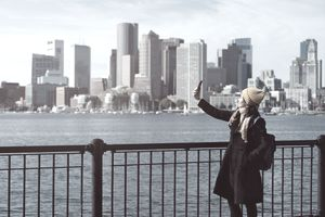 Woman taking a selfie in front of the Boston skyline.