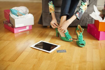 woman trying on green high heels with tablet and credit card