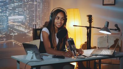 Woman with headphones on making a podcast at home at night.
