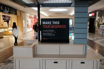 Empty retail kiosk in a mall with a sign that says,