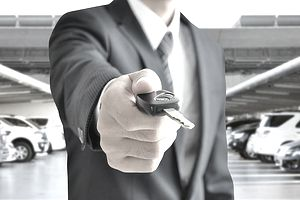man holding out car key
