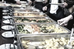 Close-up of hands scooping servings from a buffet line