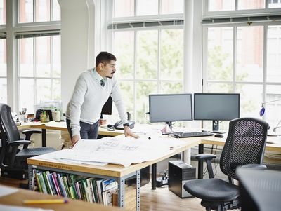 Businessman studying plans on workstation table