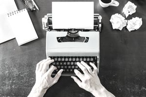 Close up of man's hands as he writes an op ed on a typewriter.