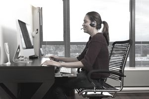 Hispanic woman in headset using computer