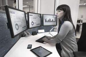 Financial analyst at keyboard in front of three computer screens