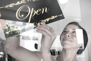 Shop assistant turning sign in shop window