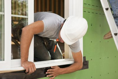 a contractor installs a window on a house