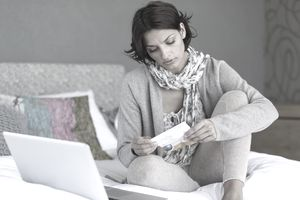 Woman looking at piece of paper in front of laptop