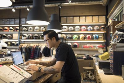 Motorcycle shop owner working at laptop behind counter