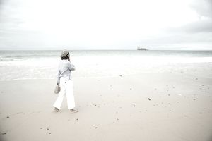 Mature woman strolling on beach chatting on smartphone, Camaret-sur-mer, Brittany, France