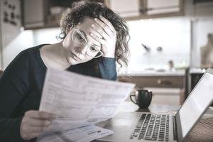 Woman looking stressed reading bills