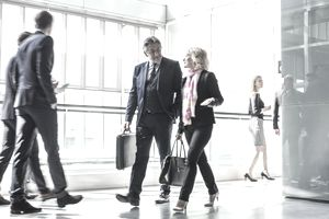 Man and woman dressed for business in a corridor.