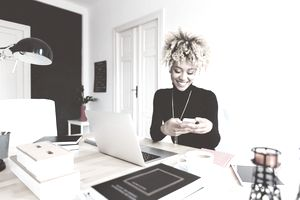 Beautiful afro american young woman sitting at the desk in a home office and using a smart phone