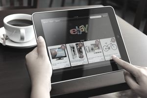 Hand holding iPad displaying eBay application
