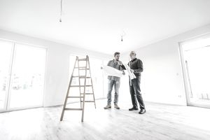 Architect checking construction plan with owner of the new home