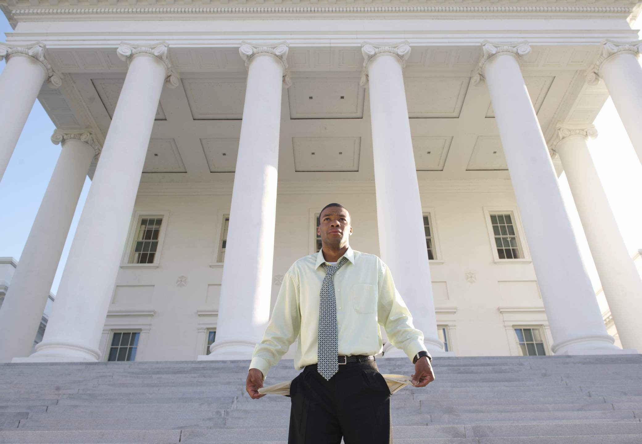 man standing in front of large white pillars showing his empty outurned pockets