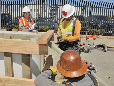 A construction forewoman is overseeing the installation of a large concrete form.