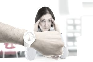 woman looking stressed with a male's arm in foreground with wristwatch