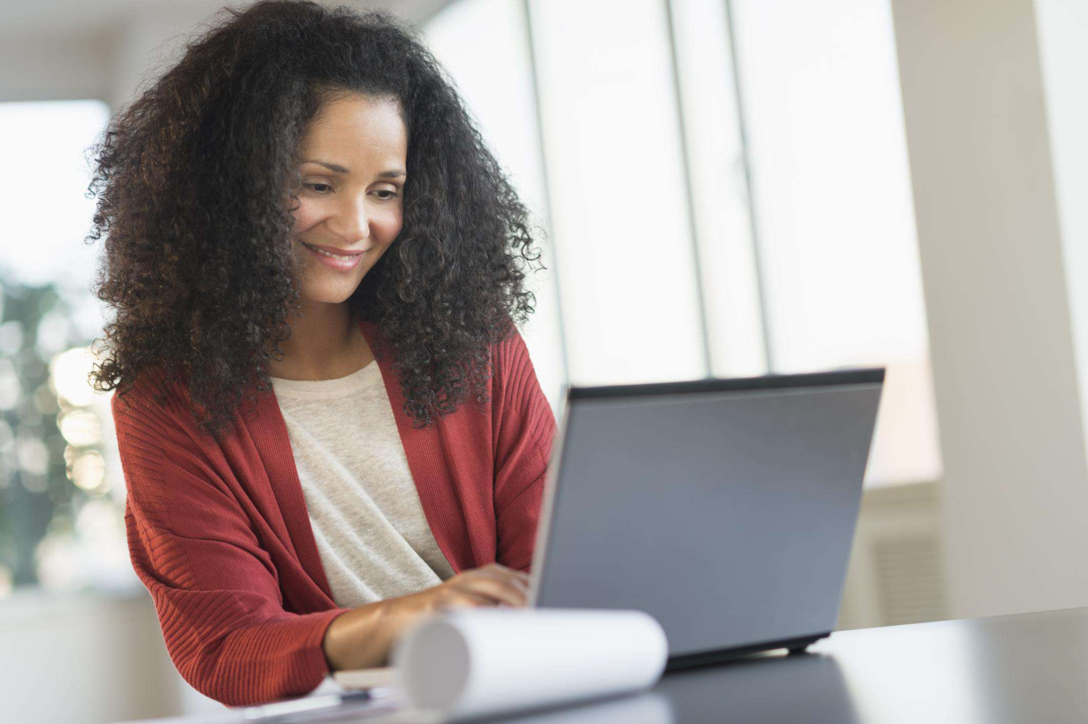 Smiling mid adult woman doing home finances with laptop