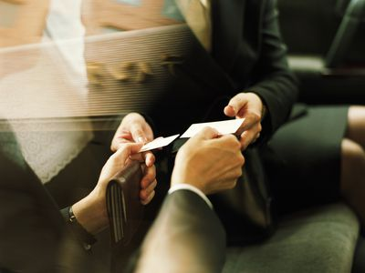 Businessman and woman exchanging business cards, close up