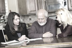 Women sitting at a kitchen table with elderly man, pointing at paperwork