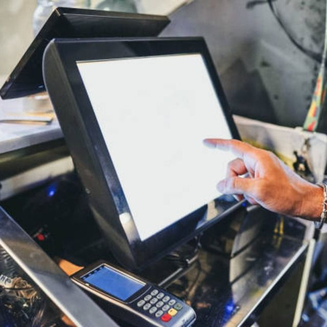 Male cashier using cafe's POS touch screen