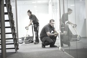 office cleaning contractors vacuuming and cleaning windows