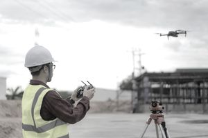 Worker in a hardhat flying a drone to a building under construction.