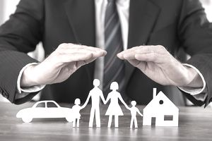 Concept of Insurance, a Man's Hands Shielding Paper Cutouts of a Family