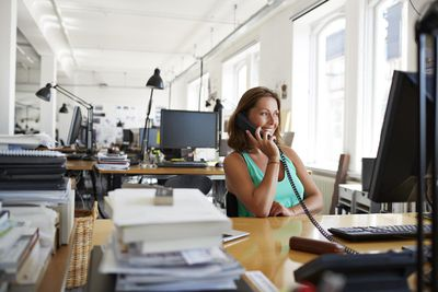 A smiling woman using good phone etiquette in an office