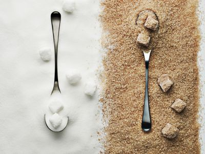 Spoon with refined sugar side by side with spoon and raw sugar.