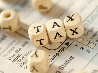 Letter cubes spelling tax on top of income tax form.