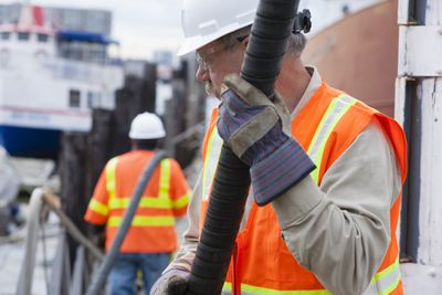 Environmental engineer extending petroleum hose for toxic waste cleanup to commercial ship