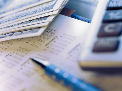 cash, calculator and calendar representing paying off a loan.