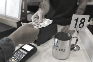 Close up customer paying cashier with cash next to tip jar
