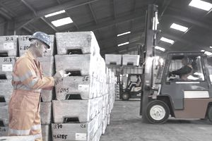 Worker inspecting metal alloy ingots on a loading dock in a port warehouse.