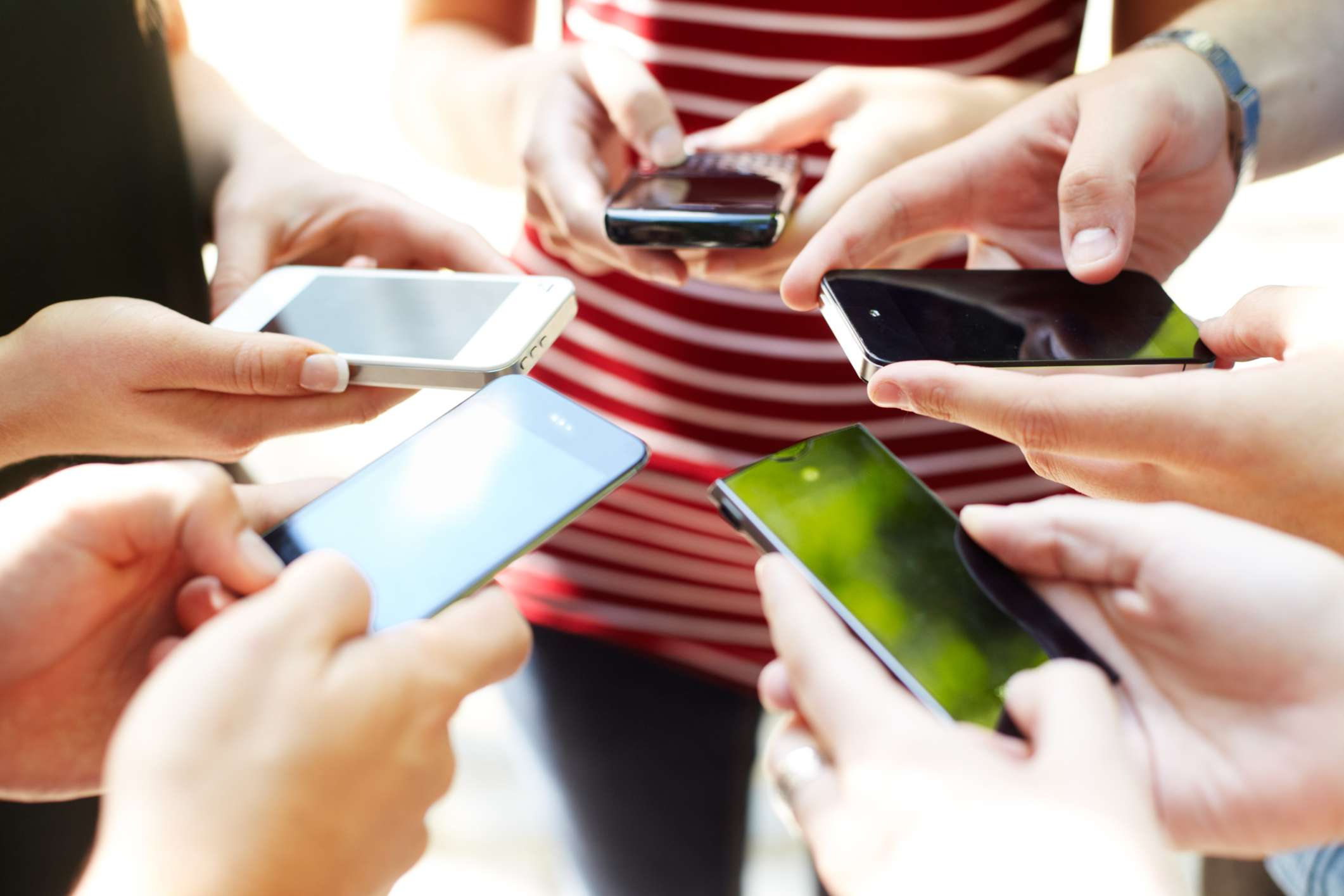 Several pairs of hands holding smartphones.