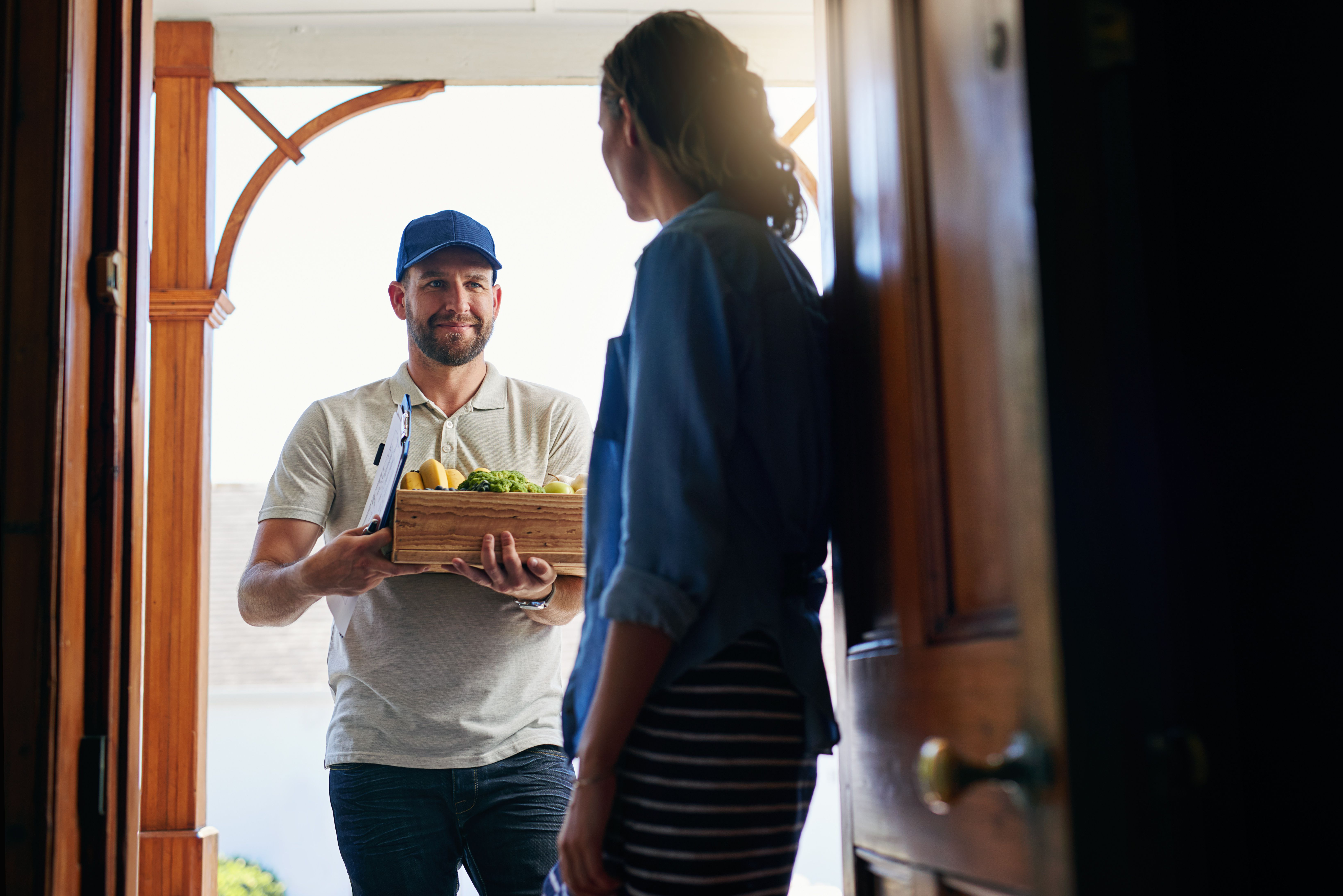 Man delivering groceries to a woman at home