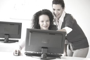 Businesswoman training employee at her desk